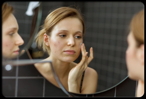 woman applying topical acne treatment to face